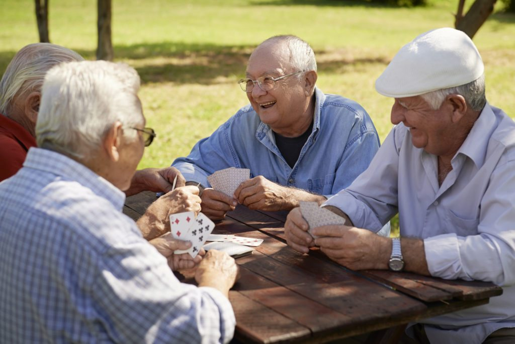 Group of older gentlemen playing cards with smiles from the Trefoil system for implants.